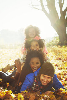 Portrait smiling young family laying on top of each other in sunny autumn leaves - CAIF05440