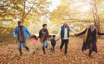 Playful multi-generation family running in autumn park - CAIF05443