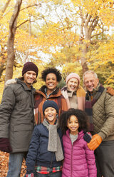 Portrait smiling multi-generation family in autumn woods - CAIF05446