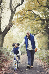 Grandfather and granddaughter bike riding on path in autumn park - CAIF05449