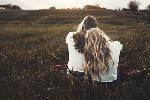 Tranquil teenage sisters in white t-shirts in rural field - CAIF05491