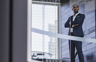 Serious, confident CEO businessman standing at modern office window - CAIF05530