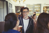 Man laughing and drinking beer with friends at bar - CAIF05542