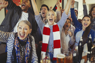 Enthusiastic sports fans cheering watching game in bar - CAIF05545