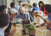 Woman enjoying birthday with friends at restaurant table - CAIF05560