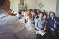 Business people in audience watching businessman leading business conference - CAIF05566