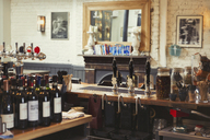Wine bottles and tap handles behind bar in empty pub - CAIF05593