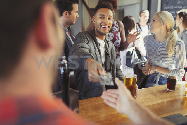 Smiling man paying bartender with credit card at bar - CAIF05602 - Paul Bradbury/Westend61