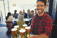 Portrait smiling bartender carrying tray of beer glasses in bar - CAIF05617