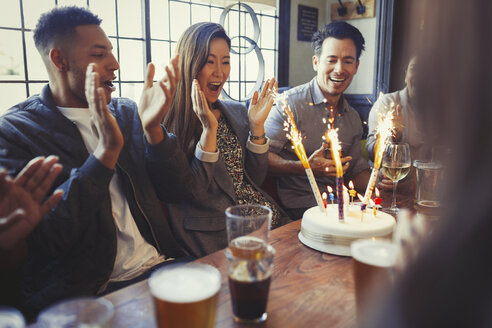Friends cheering for woman celebrating birthday with fireworks cake at table in bar - CAIF05626