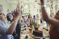 Friends celebrating birthday throwing confetti overhead at restaurant table - CAIF05632