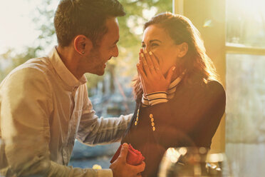 Boyfriend proposing to surprised, happy girlfriend in cafe - CAIF05653