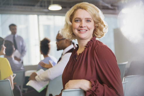 Portrait confident, smiling businesswoman in conference audience - CAIF05680