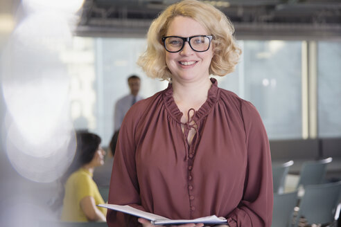 Portrait smiling, confident businesswoman with paperwork in office - CAIF05686