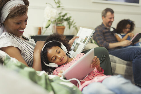 Mother cuddling daughter with headphones using digital tablet - CAIF05716