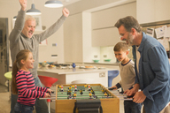 Male gay parents and children playing foosball - CAIF05731