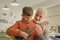 Father teaching son to play the ukulele - CAIF05734