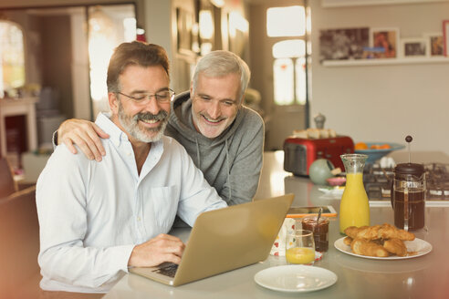 Male gay couple using laptop and eating breakfast at kitchen counter - CAIF05737