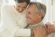 Close up affectionate mature couple hugging and smiling - CAIF05743