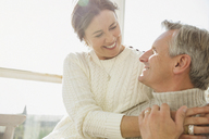 Affectionate mature couple hugging on sunny porch - CAIF05758