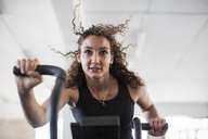 Determined young woman using elliptical trainer in gym - CAIF05767