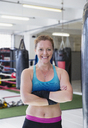 Portrait confident, smiling female boxer in gym - CAIF05779