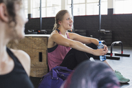 Smiling young woman resting and drinking water post workout in gym - CAIF05788