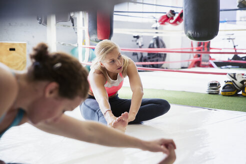Young women stretching legs next to boxing ring in gym - CAIF05794