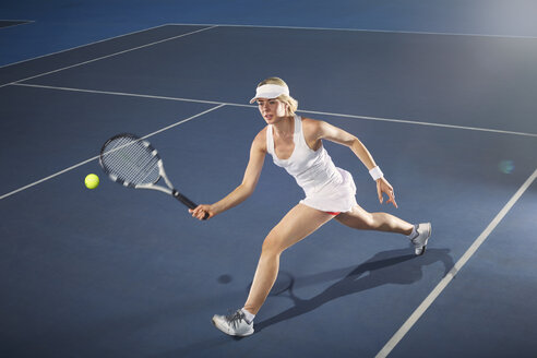 Young woman playing tennis on tennis court - CAIF05815