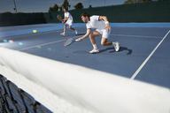 Young male tennis doubles players playing tennis on tennis court - CAIF05821