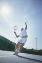 Young male tennis player playing tennis, serving the ball on sunny tennis court - CAIF05824