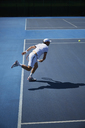 Male tennis player playing tennis on sunny blue tennis court - CAIF05827