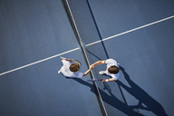 Overhead view young male tennis players handshaking at net on sunny blue tennis court - CAIF05830
