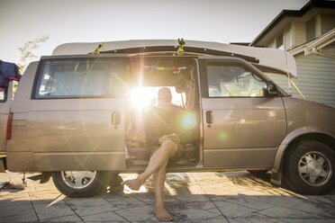 Barefoot man sitting in minivan in backlight using cell phone - GUSF00406