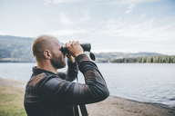 Canada, British Columbia, man looking through binoculars at Cultus Lake - GUSF00409