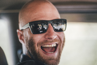 Portrait of happy young man with sunglasses and beard on a road trip - GUSF00415