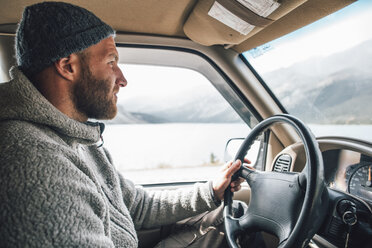 Young man with woolly hat and beard on a road trip - GUSF00421