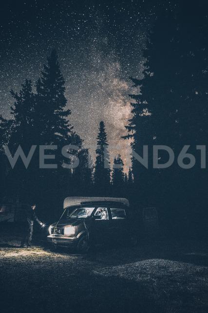 Canada, British Columbia, Chilliwack, man with torch at minivan at night - GUSF00427