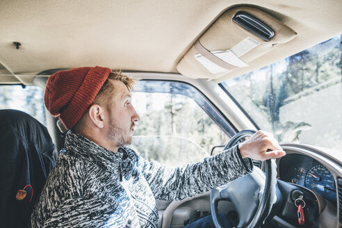 Young man with woolly hat and beard on a road trip - GUSF00430