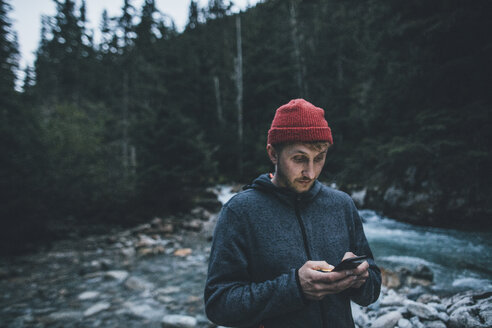 Canada, British Columbia, Glacier National Park, man with cell phone at Illecillewaet River in forest - GUSF00433