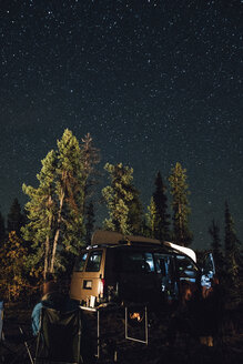 Canada, British Columbia, two men sitting under starry sky at minivan at night - GUSF00445