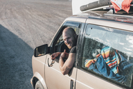 Portrait of happy young man with minivan on a road trip - GUSF00448