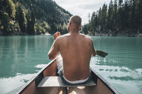 Canada, British Columbia, barechested man in canoe on Kinbasket Lake - GUSF00454