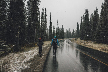 Canada, British Columbia, Yoho National Park, two men hiking on Yoho Valley Road in snowfall - GUSF00469
