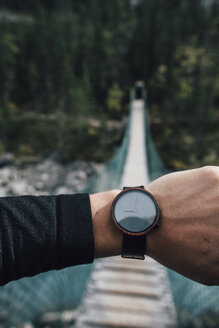 Man's hand with watch in front of swinging bridge - GUSF00475