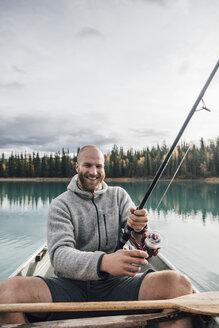 Canada, British Columbia, portrait of happy man fishing in canoe on Boya Lake - GUSF00502