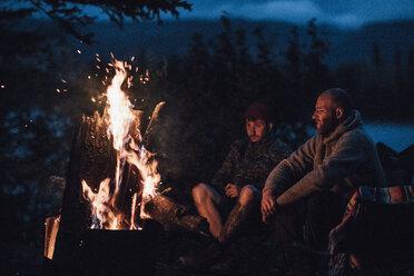 Canada, British Columbia, two men sitting at camp fire at Boya Lake at night - GUSF00514