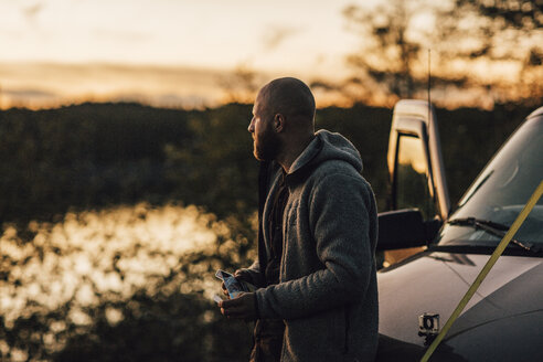 Canada, British Columbia, Port Edward, man at minivan at sunset - GUSF00517