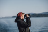 Canada, British Columbia, man looking through binoculars at the coast - GUSF00523