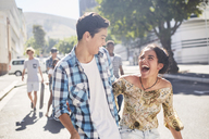 Laughing teenage couple on sunny urban street - CAIF05926